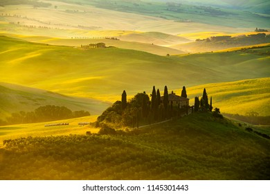 TUSCANY, ITALY - JUNE 10, 2018 : View of beautiful hilly Tuscan field in the golden morning light with farm house Cypress tree and hay bales in Valdorcia Italy