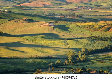 Tuscany, Italy - May 26, 2017: Magnificent spring rural landscape.Beautiful view of typical tuscan farm house, green wave hills, cypresses trees, hay bales, olive trees, golden fields and meadows.