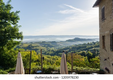 Tuscany, Italy - October 3, 2018: Morning view over the misty rolling hills by the village San Gimignano in Tuscany, Italy