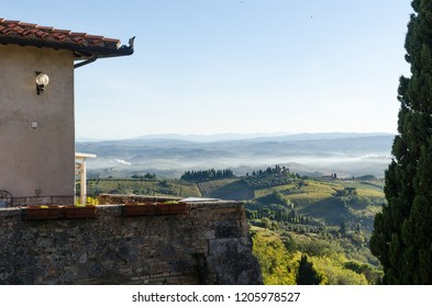 Tuscany, Italy - October 3, 2018: Morning mist by the rolling hills at the village San Gimignano in Tuscany, Italy