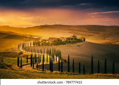 Tuscany, Italy - September 27, 2017: Beautiful Tuscany at sunset after rain. Autumn in Crete Senesi with cypress trees. Italy, Europe.
