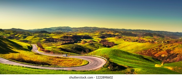 Tuscany landscape, hairpin bend road and green field at sunrise. Volterra Italy Europe