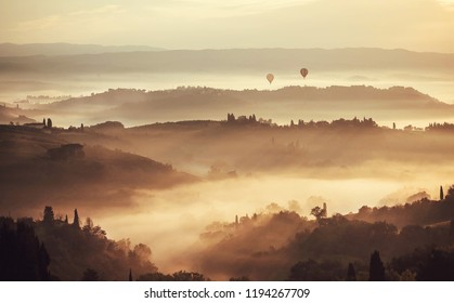 Tuscany at misty morning. Rural landscape in fog during sunrise time and hills, garden trees, mansions in province of Italy.