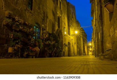 Tuscany stone village with street lamps at midnight