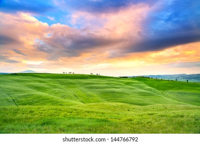 Tuscany sunset country landscape, cypress trees and green fields. San Quirico Orcia, Italy, Europe.