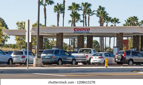 Tustin, CA, USA - October 15, 2018: Long line of cars waiting at Costco gas station.  People waiting to save cents off per gallon at the pump. Covered structure with blue and red company logo.