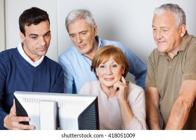 Tutor Assisting Senior People In Using Computer At Class