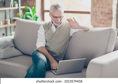 Tutor education modern technology concept. Hello hi! Cheerful excited joyful intelligent clever glad relaxed grandpa using netbook telling relatives friends news via internet connection