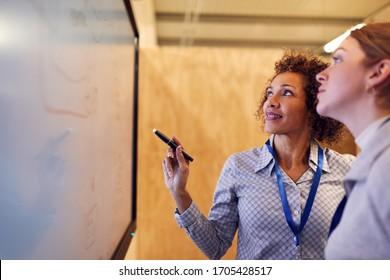 Tutor With Female Trainee Electrician Looking At Wiring Diagram On Screen