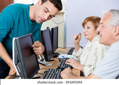 Tutor Guiding Senior Students In Using Computer At Classroom