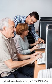 Tutor Helping Senior Woman In Using Computer