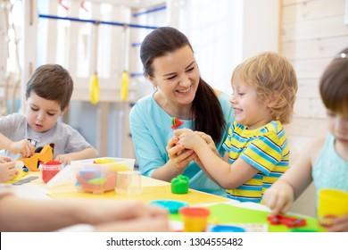 Tutor teaches children handcraft in kindergarten or playschool