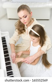 Tutor teaches little girl to play piano. Concept of music study and leisure