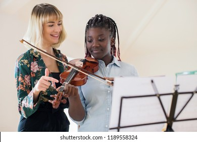 Tutor Teaching High School Student To Play Violin In Music Lesson