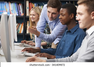 Tutor Working With Group Of Teenage Students Using Computers