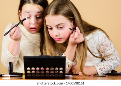 Tutorial for beginners. Little girls doing face painting and makeup tutorial. Beauty tutorial for young skin. Small artists sharpening their makeup skills with tutorial or masterclass.
