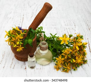 Tutsan flowers  and natural oil on a wooden background
