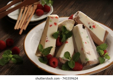 Tutti Frutti Ice Cream Cake. Slices of tutti frutti ice cream layered with chocolate or coffee ice cream are arranged on a white ceramic plate and garnished with fresh raspberries and mint leaves.