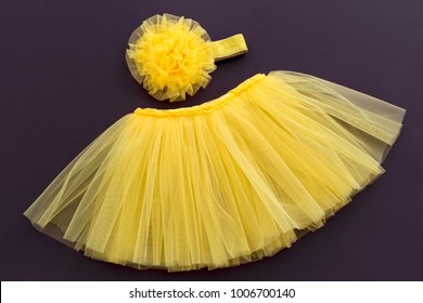 Tutu yellow skirt with flower headband for newborn girl. Concept of children's clothing.