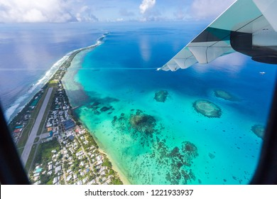 Tuvalu island lagoon under the wing of an airplane. Aerial view of Funafuti atoll and airstrip of airport in from air. Vaiaku, Fongafale motu. Island nation in Polynesia, South Pacific Ocean, Oceania.