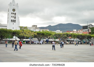Tuxtla Gutierrez, Mexico - January 15, 2015: People stroll the huge main square of the modern city of Tuxtla Gutierrez, the capital of Chiapas State. Saint Mark's Cathedral is seen in the background