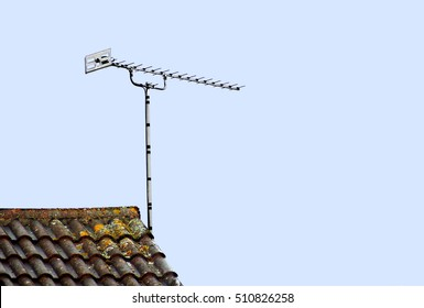A tv aerial on a tiled roof top isolated against a clear blue sky