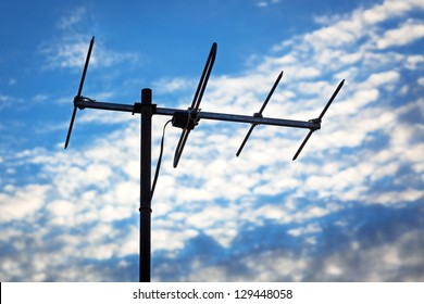 TV antenna on a background cloudy sky
