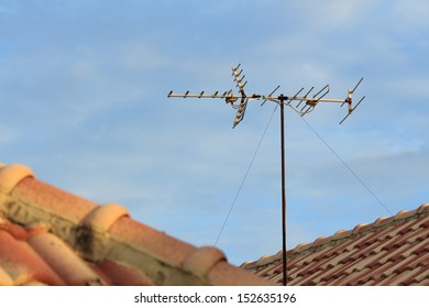 TV antenna on roof top over blue sky
