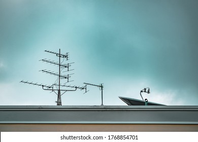 TV Antenna and Satellite dish with Blue Sky Background. Television antenna and satellite antenna on the roof. The old technology before Digital era.