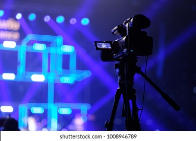 TV camera in a concert hall with laser lighting. Professional digital video camera.