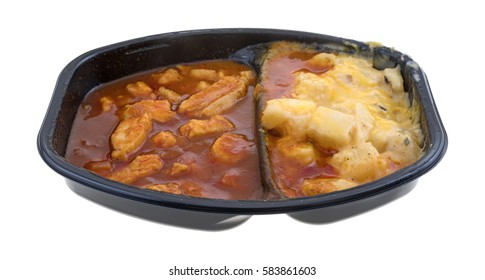 TV dinner with chunks of chicken in a thick barbecue sauce plus cheese covered potatoes isolated on a white background.