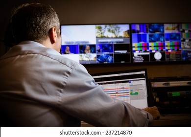 TV director at editor in studio. TV director talking to vision mixer in a television broadcast gallery.Man sat at a vision mixing panel in a television studio gallery