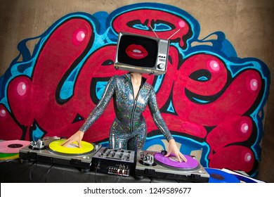 Tv head woman djing infront of the word love graffiti painted on a wall