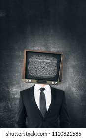 TV headed businessman standing on concrete wall background. Brainwash and control concept