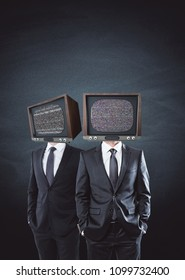 TV headed businessmen standing on concrete wall background. Brainwash and control concept