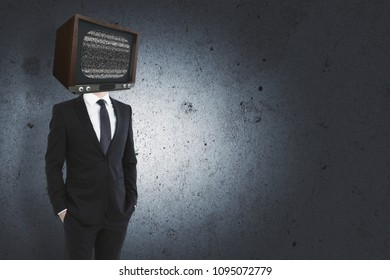 TV headed businessperson standing on concrete wall background with copy space. Manipulation concept