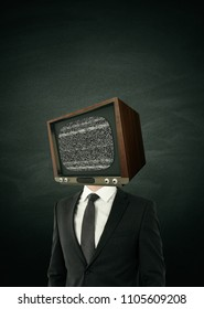 TV headed businessperson standing on concrete wall background. Brainwash and control concept