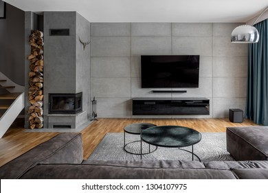 Tv living room with cement wall and wall mounted fireplace