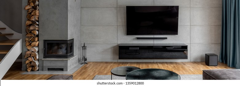 Tv living room with cement wall and wall mounted fireplace, panorama