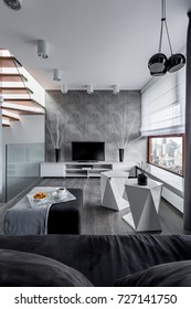 Tv living room with cement wall and modern pendant lamp