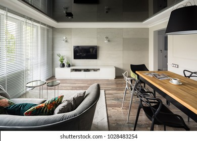 Tv living room with modern sofa, wooden table and black stretch ceiling