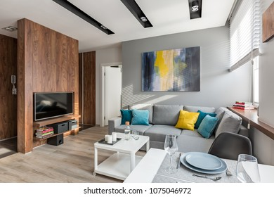 Tv living room with wooden wall, sofa and dining table