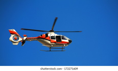 TV news helicopter with blur propeller at blue sky