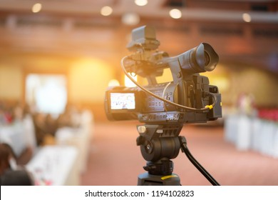 Tv OB camera in a concert or conference hall.Video cameras operator working with his equipment, Cameraman in a meeting room, light Bokeh in Background, selective focus.Vintage filtered photo process.