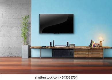 Tv on light blue wall with wooden table and plant in pot living room interrior