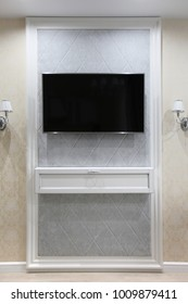 TV on the wall with a decor and two sconces on the sides
