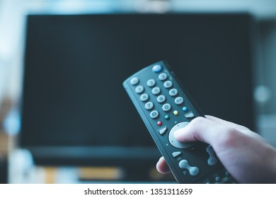 TV remote control in the foreground, tv in the blurry background. Film night with vod streaming.