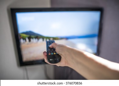 TV and remote control. Hand hold remote.