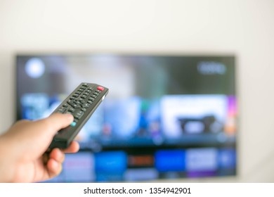 TV remote control In the hands that are pressing to change channels.