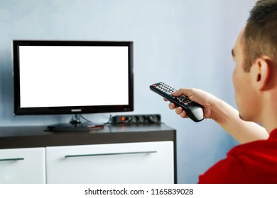 TV remote control in male hand in front of widescreen TV set with blank screen on blue wall background. Young guy switches channels on the remote from the TV.